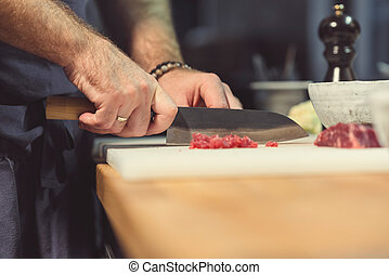 Professional chef cutting meat in the kitchen