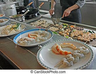 professional chef prepares dishes with vegetables and meat cooked on a griddle