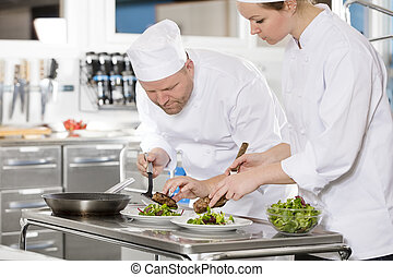 Professional chefs prepare steak dish at restaurant - Two...