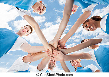 Professional Cleaners Piling Hands Against Sky - Directly...