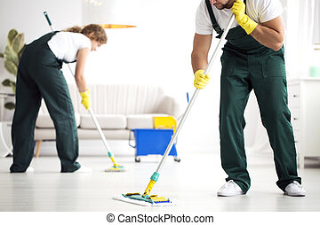 Professional cleaning crew washing floor