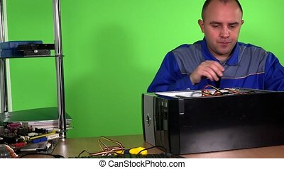 Professional computer repairer man replace power supply in desktop pc. Green wall background. Static shot. 4K UHD