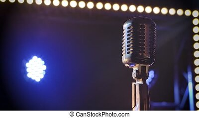 Professional concert vintage glare microphone for record or speak to audience on stage in empty retro club close up. Shot against a smoky background with bright spotlights and studio lights beams.