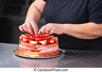 Professional confectioner making a delicious cake in the pastry shop.