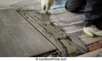 Professional constructor applying cement on floor and laying...