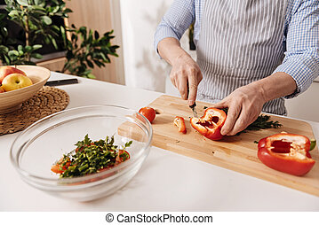 Professional cook cutting pepper for dinner in the kitchen