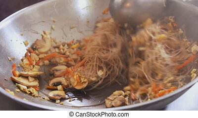 Professional cook frying noodles and vegetables at the...