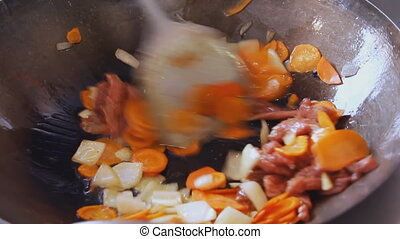 Professional cook frying vegetables and meat at the street...