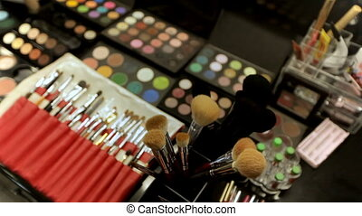 Professional cosmetics makeup artist on the table in the studio. Multicolored lipstick, shadows and a variety of cosmetic brushes