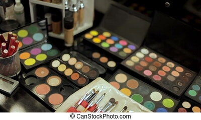 Professional cosmetics makeup artist on the table . Multicolored lipstick, shadows and a variety of cosmetic brushes