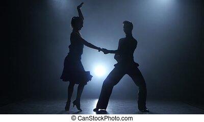 Professional couple of jive dancers posing in smoky studio, silhouette