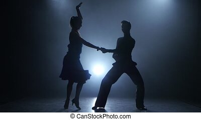 Professional couple of jive dancers posing in smoky studio, silhouette