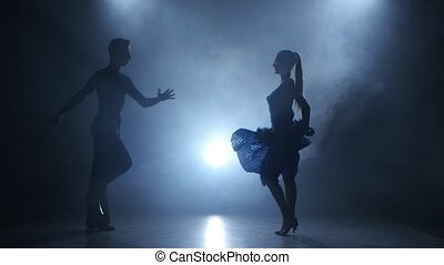 Professional couple of salsa dancers posing in smoky studio, silhouette