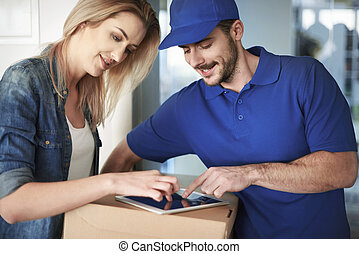Professional courier delivering package to woman