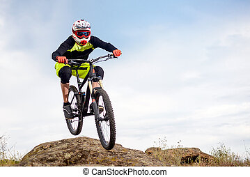 Professional Cyclist Jumping over Rock on the Mountain Bike on the Rocky Hill. Extreme Sport Concept. Space for Text.