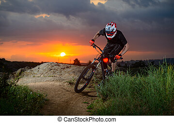 Professional Cyclist Riding the Bike on the Mountain Rocky Trail at Sunset. Extreme Sport
