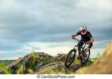 Professional Cyclist Riding the Bike on the Rocky Trail. Extreme Sport.