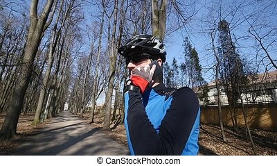 Professional cyclist speaks by phone in park
