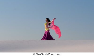 Professional dancer in the sandy desert in the hands of a...