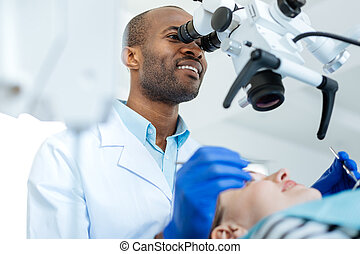 Professional dentist conducting checkup of cavity with microscope