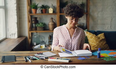 Professional designer is looking through notebook with design samples then taking splash-paper and choosing colors for new collage. Work and ideas concept.