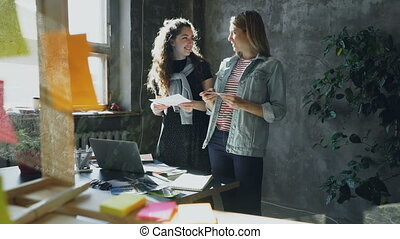 Professional designers are standing in light office and choosing pictures for exhibition. They are discussing photos, sharing ideas, putting illustrations on table and laughing.