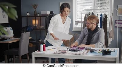 Professional male and female designers consulting with with other about sketches at modern atelier. Two fashion people coworking on new clothing collection.