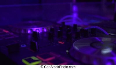 Professional dj equipment for mixing and record dance music o in night club. Close up musicequipment and DJ control console with colorful light in nightclub. Night life concept.