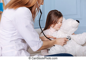 Professional doctor examining fluffy toy of little grl