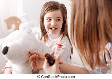 Professional doctor giving pills to little girls toy
