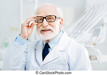 Professional doctor touching his glasses