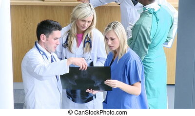 Professional doctors examining an x-ray in hospital footage...