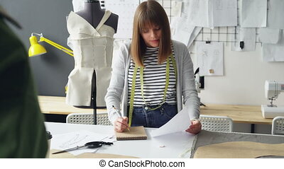 Professional dressmaker is making notes in notepad and...