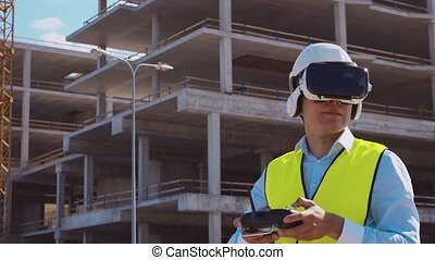 Professional drone operator in virtual reality helmet standing in front of construction site. Builder holding remote controller. Office building and crane background. Business, real estate and investment concepts.