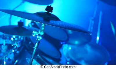 Professional drummer playing on the drum by wooden sticks...