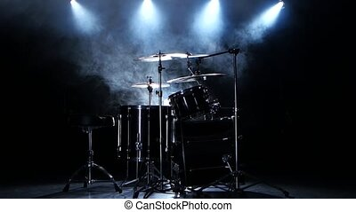 Professional drums in the studio. Black smoky background. Back light. Side view