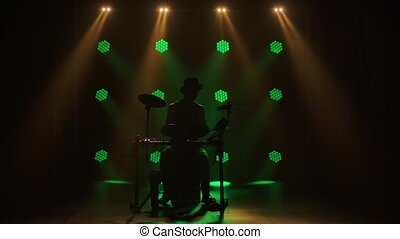 Professional drumstick musician playing drums in the dark ...