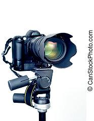 Professional digital SLR camera with telephoto zoom lens on tripod. Isolated white background,