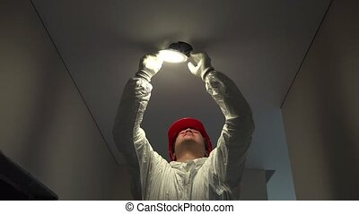 professional electrician man mount circle led light into ceiling hole. Handheld steadycam flycam movement shot. 4K UHD