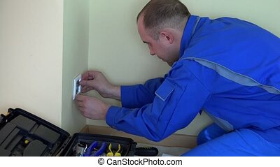 Professional electrician man working with screwdriver on outlet.