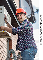 Professional electrician repairing air conditioner on outer wall of building