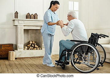 Professional experienced caregiver looking after her patient