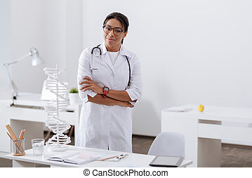 Professional experienced doctor standing in her office