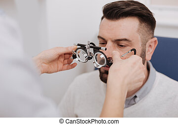 Professional experienced ophthalmologist helping her patient to wear glasses