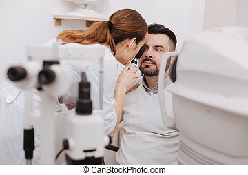 Professional experienced optometrist using an ophthalmoscope