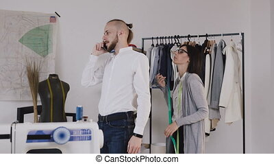 Professional fashion designer or dressmaker taking measurements for sewing suit at tailors shop. Seamstress with measuring tape makes measurements for sewinf a new jacket for her client. Customer with beard speaks by phone