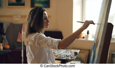 Professional female artist is working in studio painting...