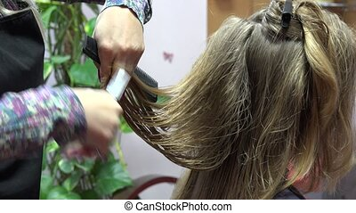 Professional female barber cuts blond woman hair with scissors. 4K