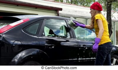 professional female car washer cleaning car window with soapy sponge.