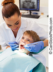 female dentist examining little patient